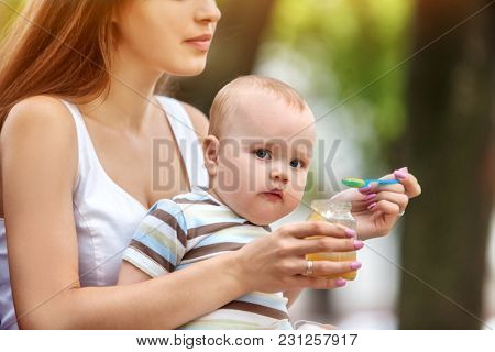 Baby feeding spoon by mother in park outdoor. Weaning in first weeks. Portrait of happy beautiful mom and eating child summer on bench. Good appetite fresh air by baby food. Vitamins for kid.
