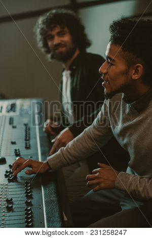 Concentrated Young Sound Producers At Recording Studio