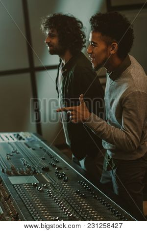 Smiling Young Sound Producers At Recording Studio