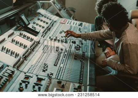 Modern Musicians Working With Graphic Equalizer At Recording Studio