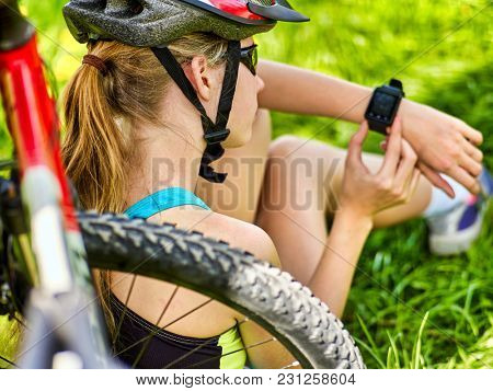 Woman traveling bicycle in summer park. Bicyclist girl watch on smart watch. Girl counts pulse after sport training. Cycling is good for health. School trip.