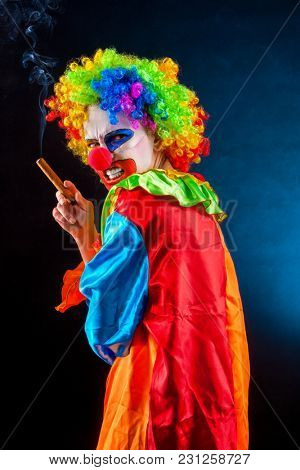 Evil clown on black background. Mad woman Halloween is smoking cigar. Portrait of crazy female with an angry look after performance. Person hates his profession and is unhappy with himself.