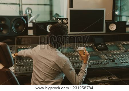 Sound Producer With Disposable Cup Of Coffee Working At Studio
