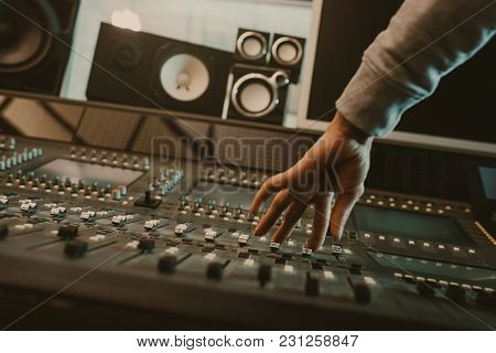 Cropped Shot Of Sound Producer Setting Graphic Equalizer At Studio