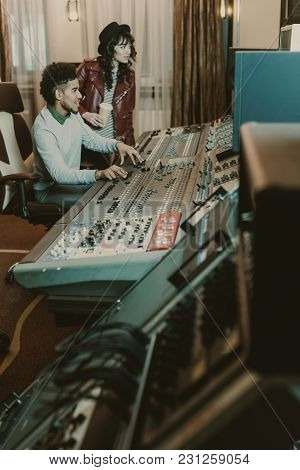 Young Successful Musicians Workign With Equipment At Recording Studio