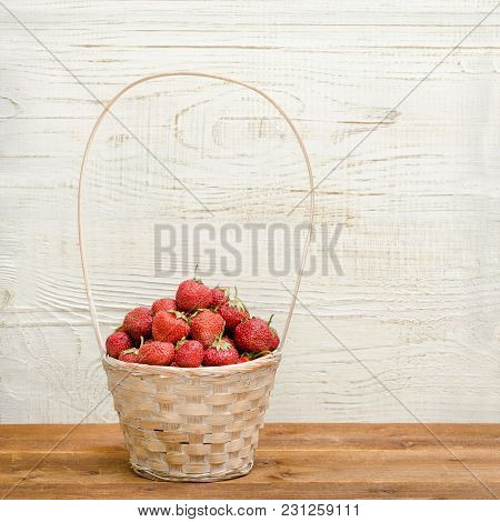 Basket Of Ripe Strawberries On A White Wooden Background. Space For Text