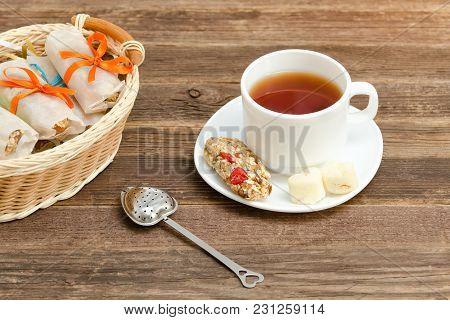 Mug Of Tea, Muesli Bars And Tea Strainer. Wicker Basket With Bars. Brown Wooden Background