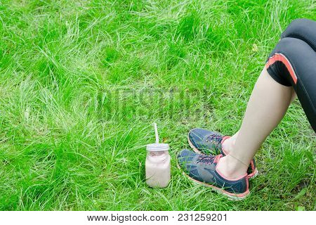 Strawberry Smoothies And Female Legs In Sneakers On Green Grass