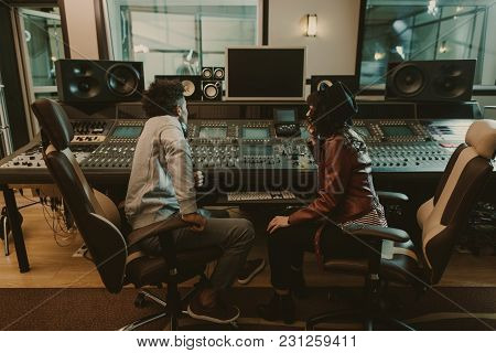 Sound Producers Sitting At Recording Studio And Discussing