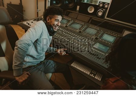 Happy Young Sound Producer Sitting At Studio