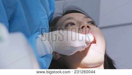 Patient checking her teeth with mirror at dental clinic