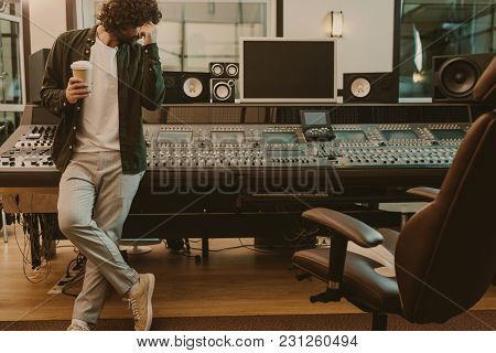 Young Sound Producer Standing At Studio With Cup Of Coffee To Go