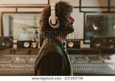 Side View Of Sound Producer In Headphones Enjoying Music At Studio