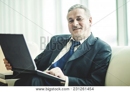 Businessman Working On Laptop Sitting On A White Sofa In A Private Office