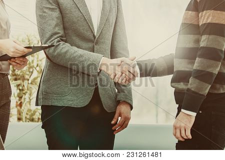 Handshake Of A Manager And A Customer On The Background Of The Office.the Photo Has A Empty Space Fo