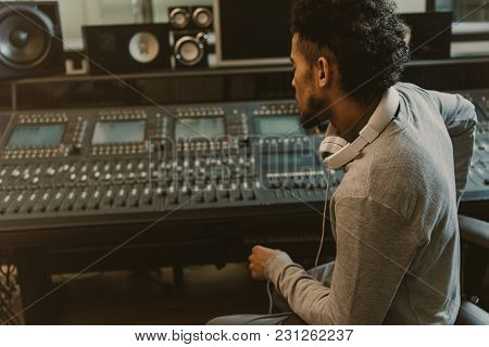 Sound Producer Sitting In Armchair And Looking At Graphic Equalizer
