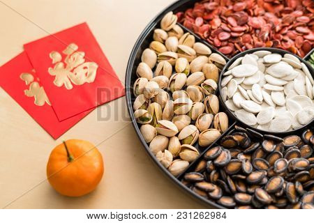 Trdaitional chinese snack tray for Lunar new year with red paket word mean luck