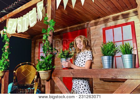 Happy little girl with a flower pot is standing on the porch of a wooden house. Household chores. Easter holidays.