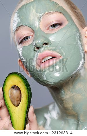 Beautiful spa woman in facial mask and avocado. Beauty, natural cosmetics concept. Spa, body care.