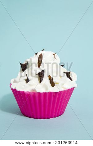 Pink Silicone Cupcake Mold Filled With Whipped Cream And Rose Thorns Sprinkles On It On A Vibrant Bl
