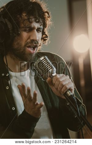 Emotional Young Singer In Headphone Performing Song At Studio
