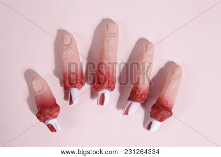 5 Fake Bloodied Plastic Fingers As If They Had Been Torn Off On A Vibrand Pink Background. Gradient
