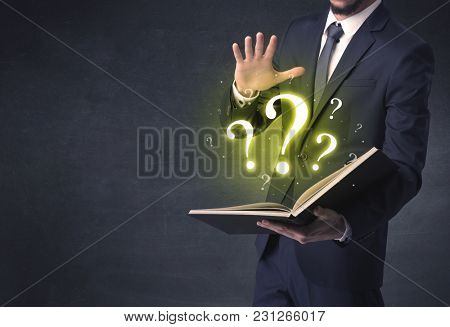 Businessman holding a book with question mark symbol.