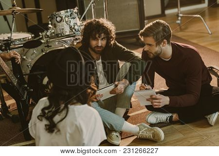 Young Band Writing Music Together While Sitting On Floor