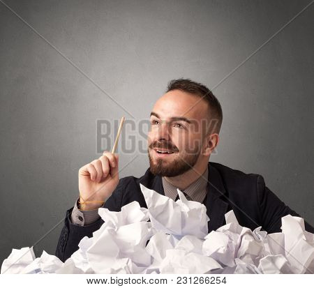 Young businessman sitting behind crumpled paper with grey background
