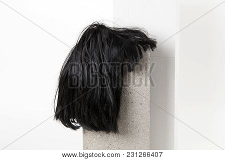A black wig put on a gray cinderblock, on a white background. Minimal funny and quirky design still life photography poster