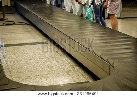 Passengers Waiting At The Airport Luggage Conveyor Belt.
