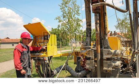 Geothermal Drilling Rig Equipment. Worker Operating Drilling Rig Control Panel.