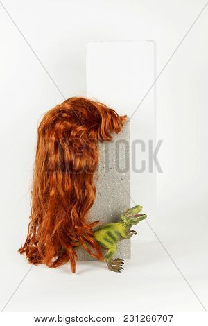 A Long Red Wig Put On A Gray Cinderblock With A Figurine Dinosaur Hidding Behind On A White Backgrou