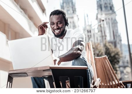 Work Is Calling. Low Angle Of A Friendly Looking African American Guy Smiling Cheerfully While Talki