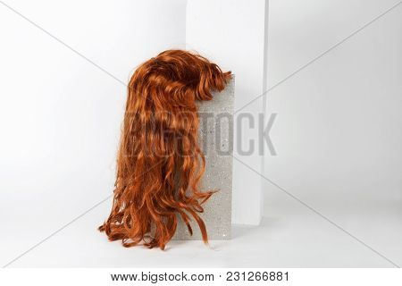 A Red Wig Put On A Gray Cinderblock, On A White Background. Minimal Funny And Quirky Design Still Li