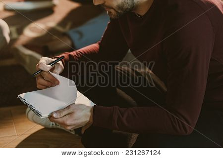 Cropped Shot Of Handsome Young Man Holding Blank Notepad