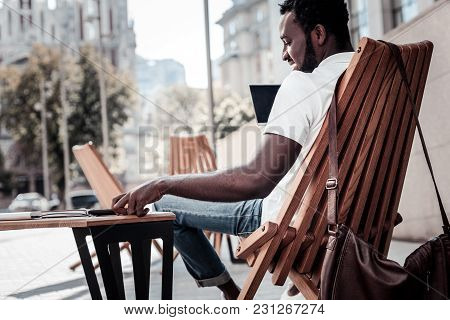 Young And Successful. Positive Minded Self Employed Guy Smiling While Relaxing On A Wooden Chair Wit