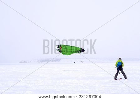 Skier-snowkiter Catches The Wind During A Snowfall