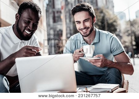What Do You Think. Happy Young Men Smiling Cheerfully While Sitting Next To Each Other And Looking A