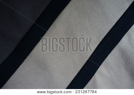 Pair Of Black Ribbons Sewn To Grey And Beige Fabric