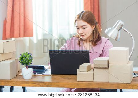 Young Happy Asian Online Business Woman Working On Her Computer At Home In Her Bedroom, Surrounded B