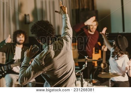 Singer Stretching Hand To Happy Music Band While They Having Repetition