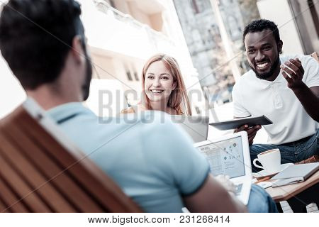 Always Working As A Team. Friendly Coworkers Sitting Outdoors And Grinning Broadly While Discussing