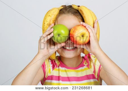 Cheerful little girl with apples, lemon and banana poses  in studio