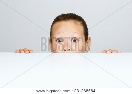 A little girl hides under the table for fear