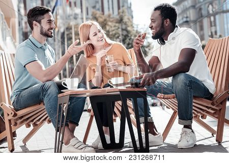 Never Getting Bored Together. Three Young Mates Grinning Broadly While Enjoying A Pleasant Conversat