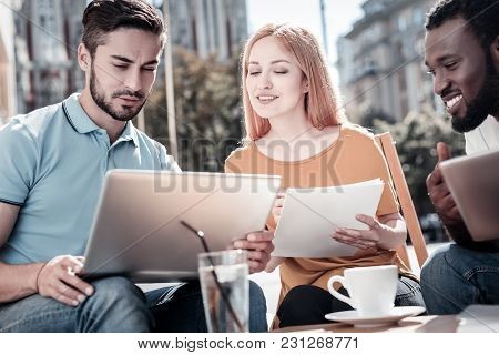 Let Me See. Millennial Businesspeople Sitting Outdoors And Discussing Business Documents While Worki