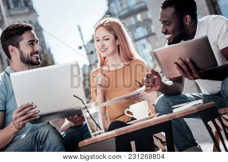 What Do You Think About That. Cheerful Young People Reuniting Over A Business Project And Sharing Th