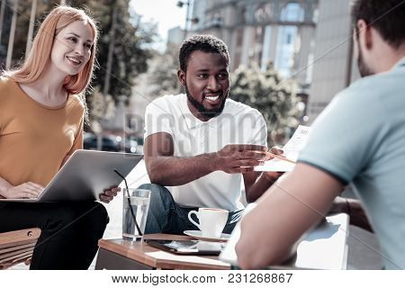 Have You Seen This. Enthusiastic Entrepreneurs Sitting Outdoors And Working With Business Documents
