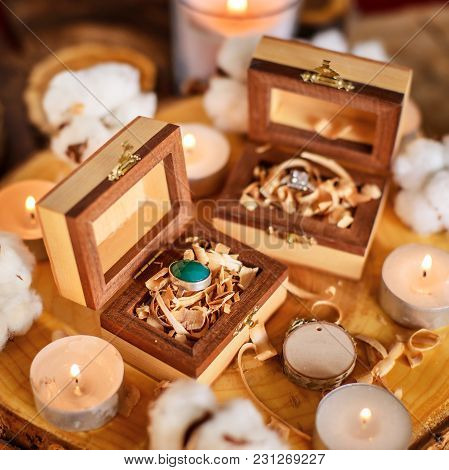 Two Beautiful Handmade Wooden Boxes With Rings On Wooden Background With Candles And Cotton Flowers